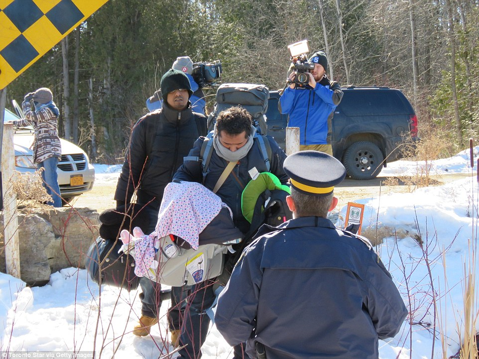 A group of asylum seekers  two men, a woman and a baby  cross the border illegally from the United States into Canada near Saint-Bernard-de-Lacolle, Quebec