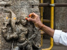 Dr Eleanor Power of the Santa Fe Institute analyzed how the nature of people's religious practice correlates with the structure of their social support networks in two villages in South India. She wanted to find out if people that show greater religiosity are more likely to undertake acts that benefit others. Pictured is a religious devotee placing red powder on a carving of Kala Bhairava at the temple of Nanjangud, South India