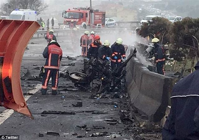 Emergency services workers inspect the charred remains of the burnt-out helicopter