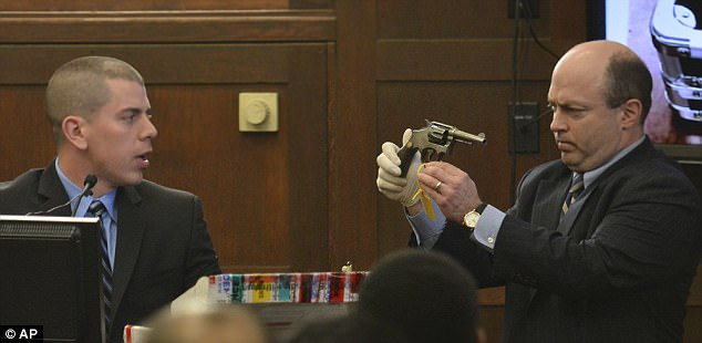 Prosecutor Patrick Haggan held the .38-caliber Smith & Wesson revolver, that was manufactured in 1913, high for police witnesses to identify in court on Monday
