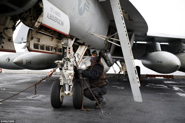 A U.S. Navy crew member works on a U.S. F18 fighter jet on the deck of USS Carl Vinson
