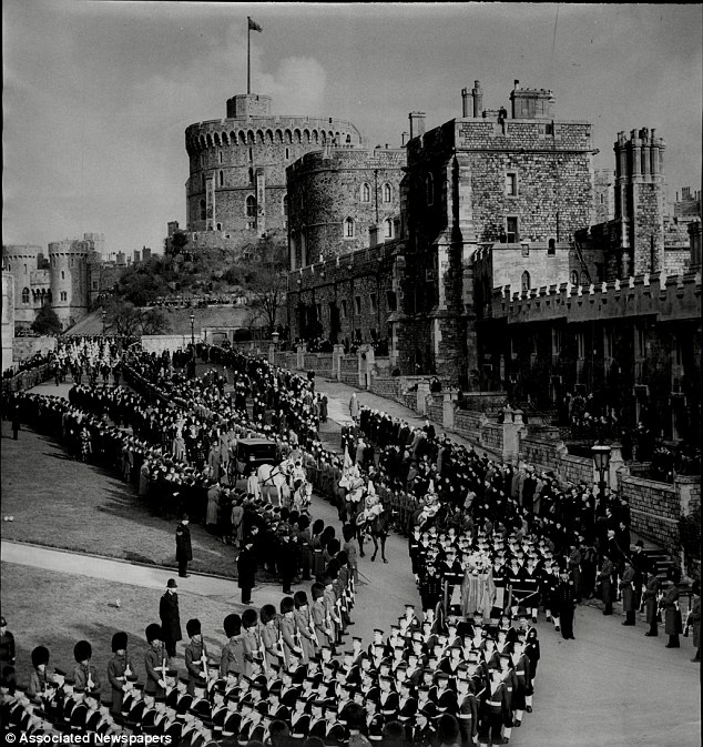 The Royal Standard at full mast flies over Windsor Castle on the hill below the coffin of King George VI followed by the carriage with Queen, The Queen Mother, Princess Margaret and The Princess Royal moves slowly towards St Georges Chapel in 1952