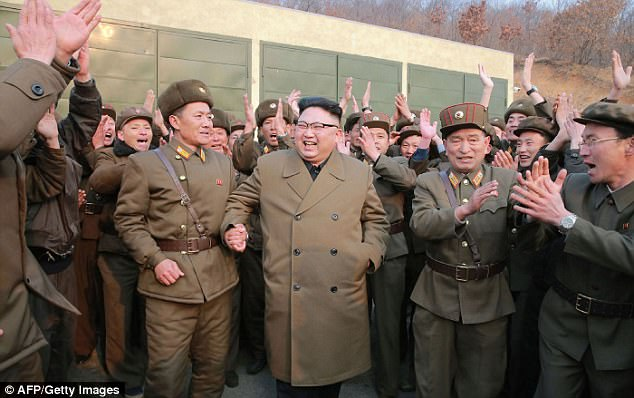 Beaming: Kim celebrated with his generals who applauded the test at the launch site