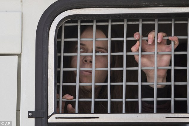 A detained woman looks out of a police bus in downtown Moscow, Russia