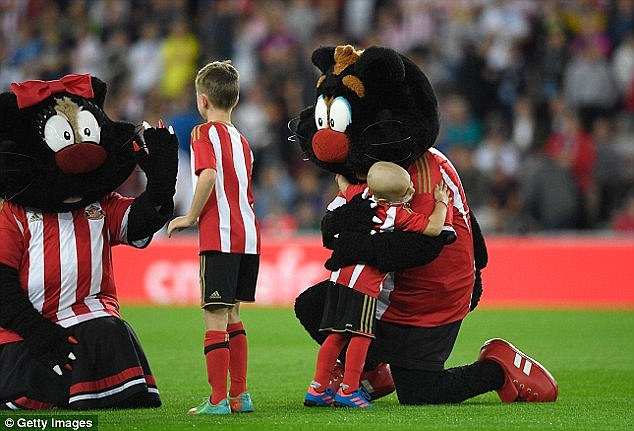 Bradley receives a hug from Sunderland mascot Samson the Cat ahead of that match