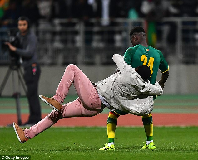 A pitch invader tackles Lamine Gassama during a match between Ivory Coast and Senegal