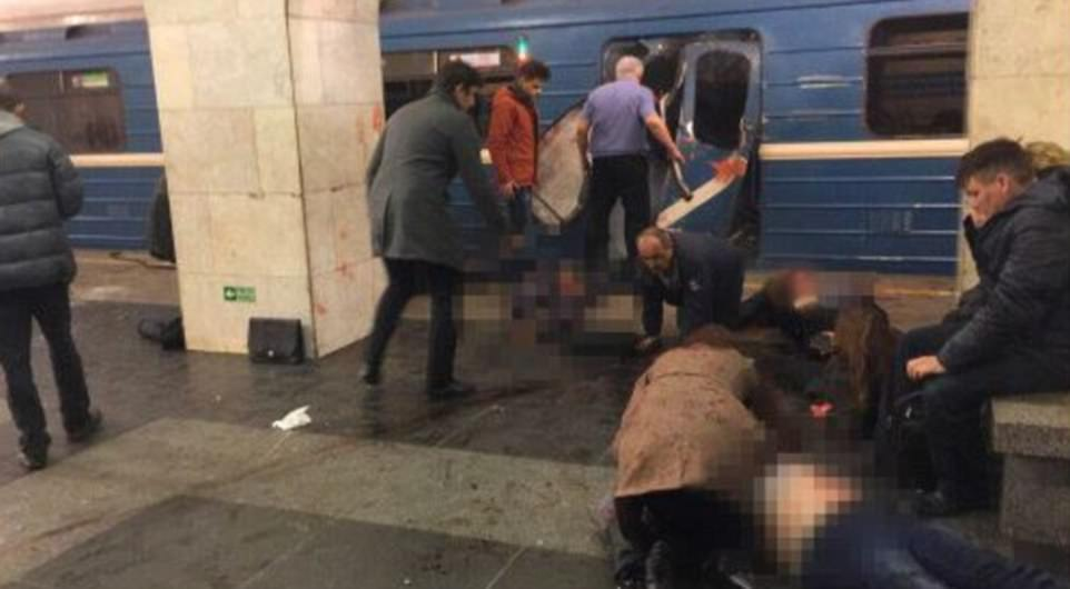 A man crawls away from the train as bloodied passengers attempt to save those injured