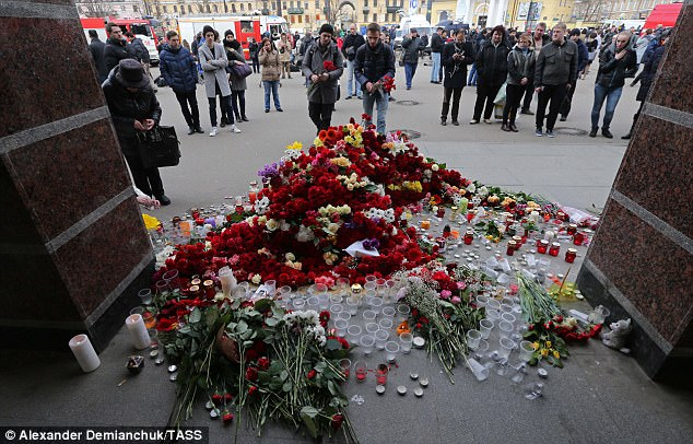 Russians lay flowers in memory of the dead outside the station where the attack happened