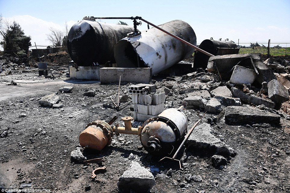 Detonated: These tanks - likely containing fuel - appear to have been blow up by the massive rockets. The Syrian media claimed nine civilians died even though the attack was launched at almost 4am local time on a military base