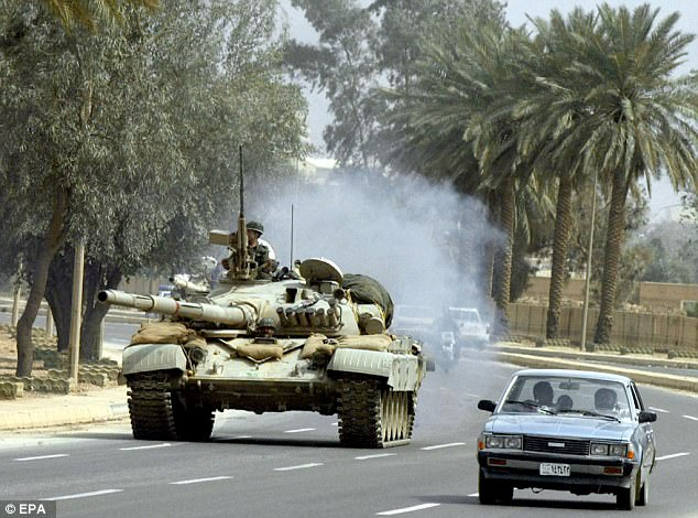 An Iraqi T-72 tank rumbles down a road near Baghdad in 2003, prior to the invasion by a US-led coalition. Many of Saddam Hussein's tanks were left behind in Kuwait after British and American forces liberated the country in 1991 (file picture)
