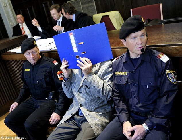 Fritzl covers his face during his trial in 2009. Perry observed: 'His eyes were cold and piercing. No remorse, no compassion, for anyone on earth but himself. No tears. Nothing'