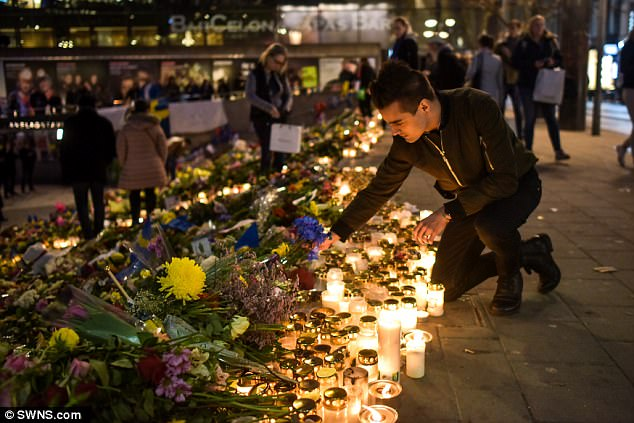 Light in the dark: Flowers and candles spread out across the scene of the terror attack in Stockholm as thousands paid their own personal tribute to the four victims killed by a careering truck