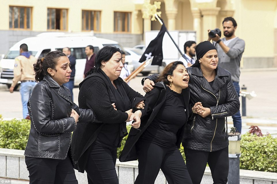 Women in black cry outside the funeral for those kille. Women wailed as caskets marked with the word 'martyr' were brought into the Mar Amina church