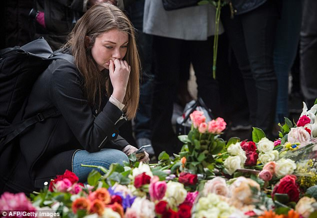 He also left 15 wounded after ploughing a stolen beer truck through crowds of people in one of the Swedish capital's busiest shopping districts. Pictured, members of the public lay flowers at the scene