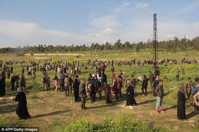 Syrians, evacuated from Fuaa and Kafraya, flee into a field near the site of a suicide car bombing