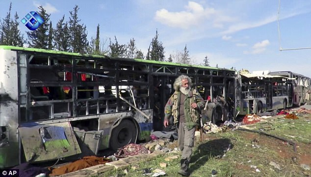 A gunman passes by the buses that were damaged in a blast at the Rashideen area, a rebel-controlled district outside Aleppo city