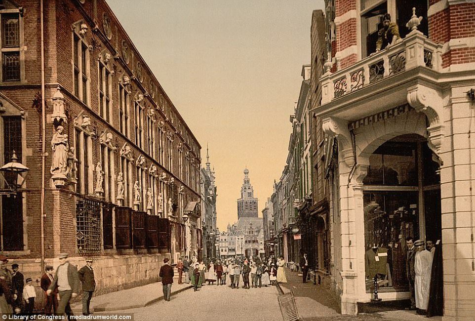 Pictured here is the town hall and great market at Nymegen. Three men can be seen watching the photographer on the right