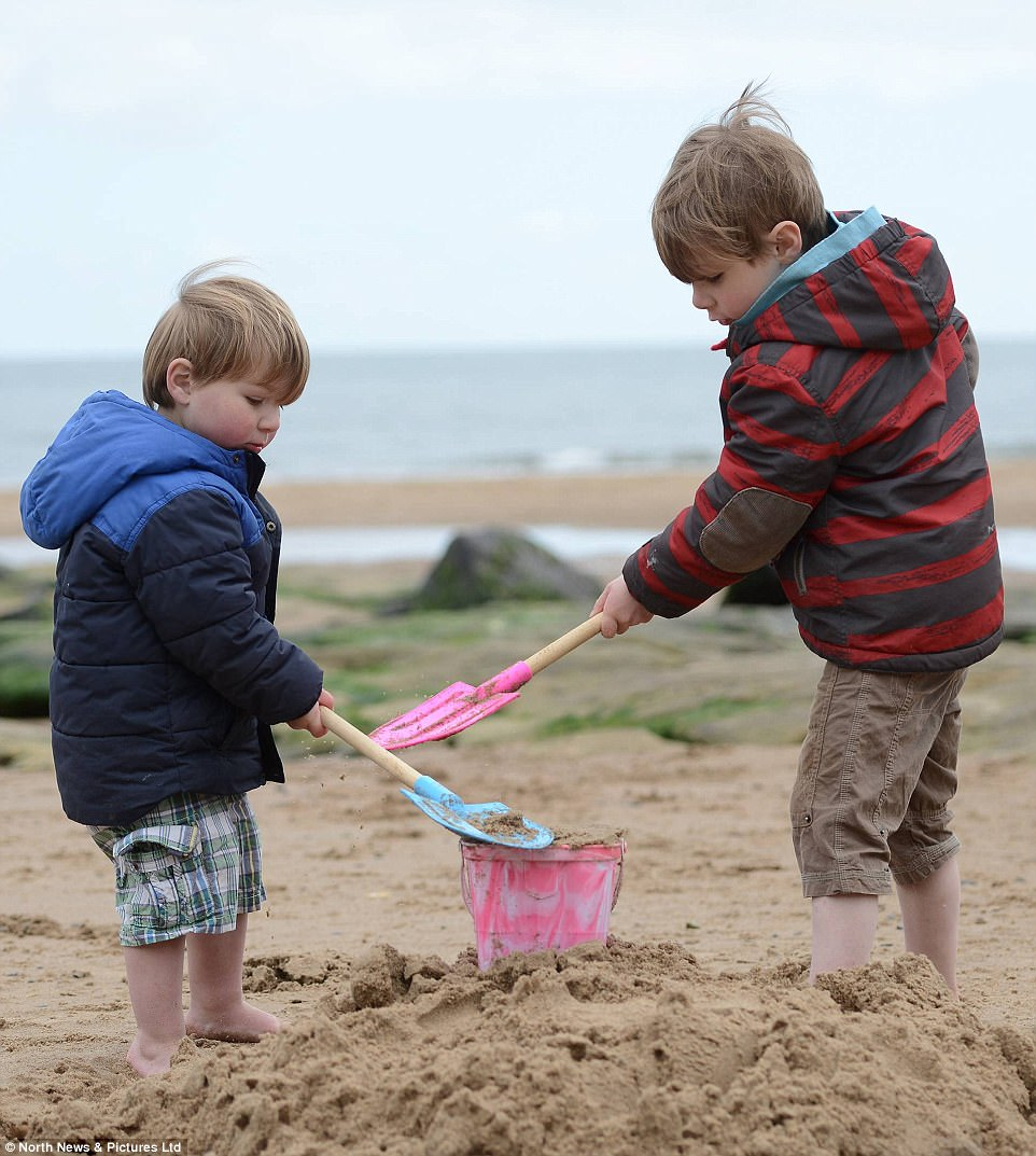 Brothers Archie, left, four, and Sholto, two, right, wrap up warm at Tynemouth just days after Britain enjoyed fine and warm weather