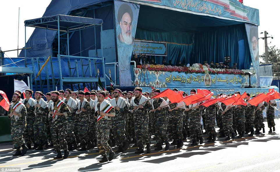 Iranian soldiers wearing camouflage, with white sashes, red headbands and red flags pass by the grandstand during the parade