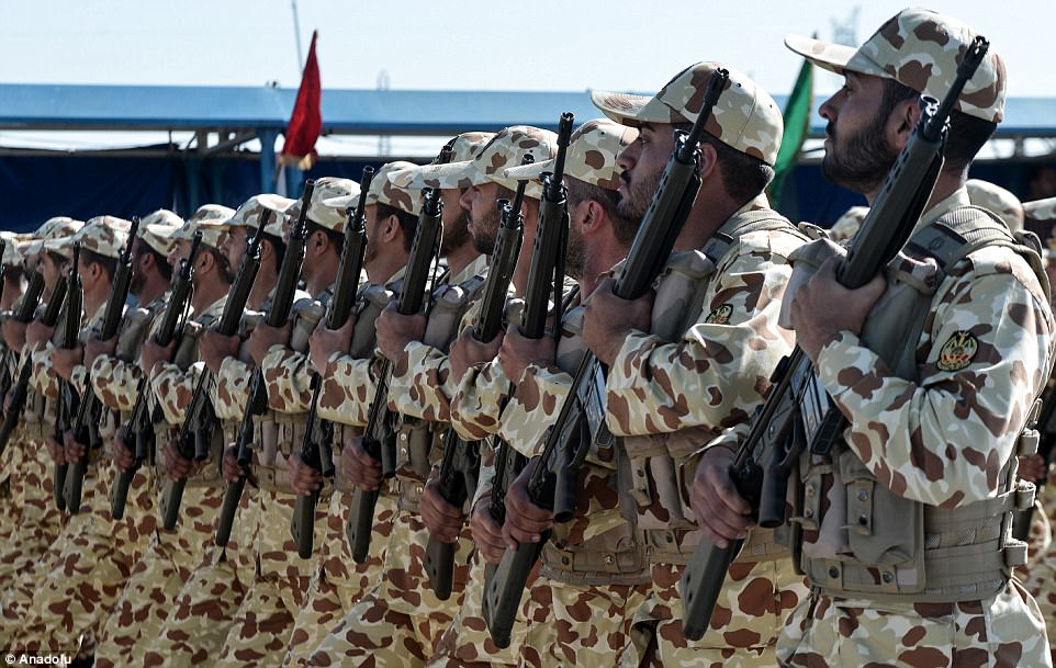 Dozens of soldiers kitted out in traditional camouflage hold their assault rifles to their chests and over their left shoulders