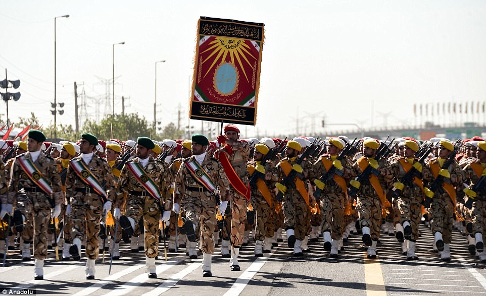 Iranian soldiers in elaborate and colourful uniform march in unison as they carry their weapons and glace at the grandstand
