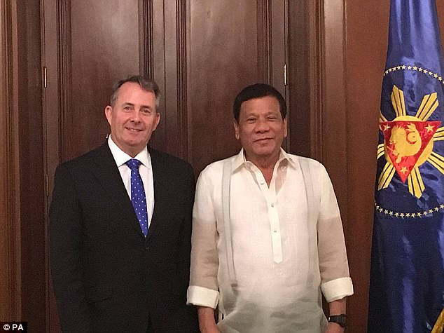 It also claims that civilian members of the so-called Davao Death Squad, which rights activists allege killed hundreds of people in Duterte's hometown of Davao, were drafted to 'augment and assist' the police's current nationwide anti-drug operation. Pictured, Duterte with Trade Secretary Liam Fox)