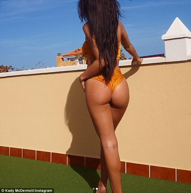 Cheeky side: The brunette beauty raised temperatures in a orange two piece, which made the most of her killer abs and her very pert derriere