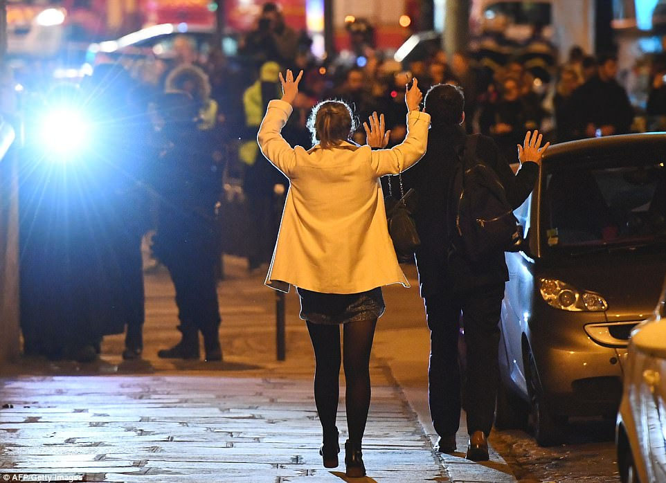 People held their hands up as they walked towards officers close to the scene where a policeman was fatally shot in Paris