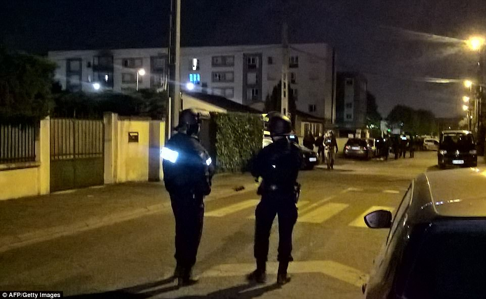 Police officers searched the home of the suspected gunman in east Paris following the attack in the capital on Thursday