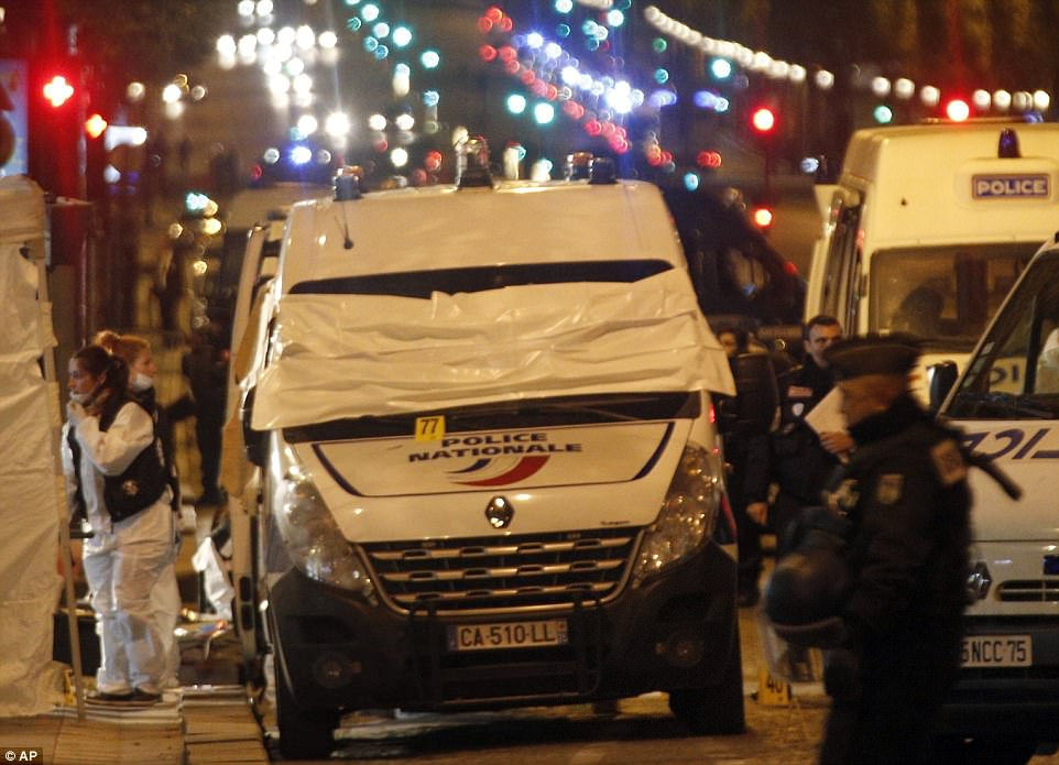 Forensic experts and police officers were seen examining evidence from a van on the Champs Elysees in central Paris