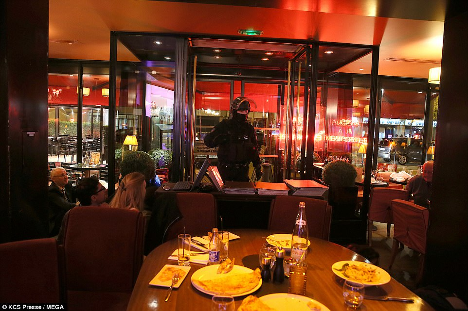 An armed policeman speaks to diners in a nearby Parisien restuarant, who cowered to the floor in fear of the ISIS gunman