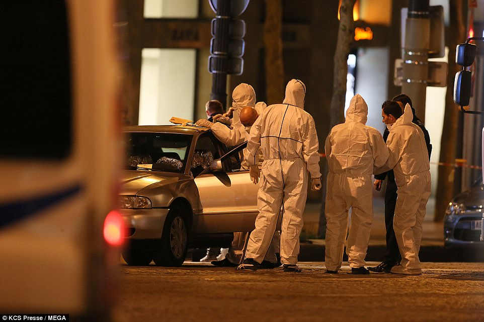 A team of forensic detectives examine the Audi, which the gunman was driving. ID of Karim Cheurfi was found in the vehicle