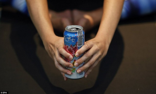 One fitness fanatic holds a Thai drink in her hands as she pulls off a perfect butterfly pose