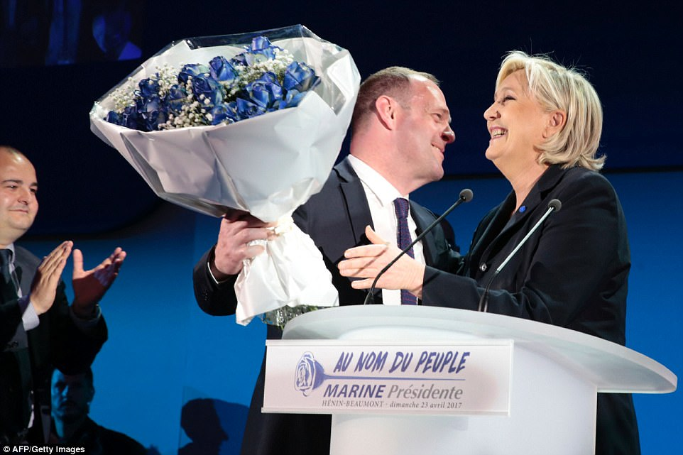 She added: 'It is time to liberate the French people from the arrogant [political] elite.' Le Pen was later given a bunch of flowers