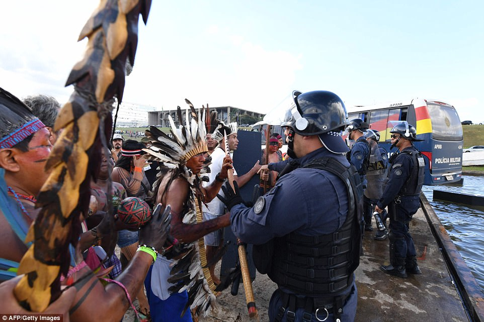Tribe members in traditional costume and dress use traditional weaponry in a stand-off with police in Brasilia, during the annual march for rights