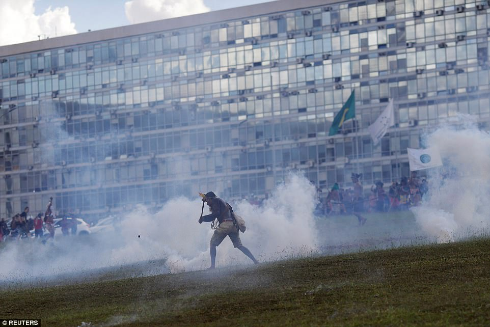 A man stands on his own as smoke billows around him during the protests. The police have used tear gas against the protesters, claiming they got too close to Congress