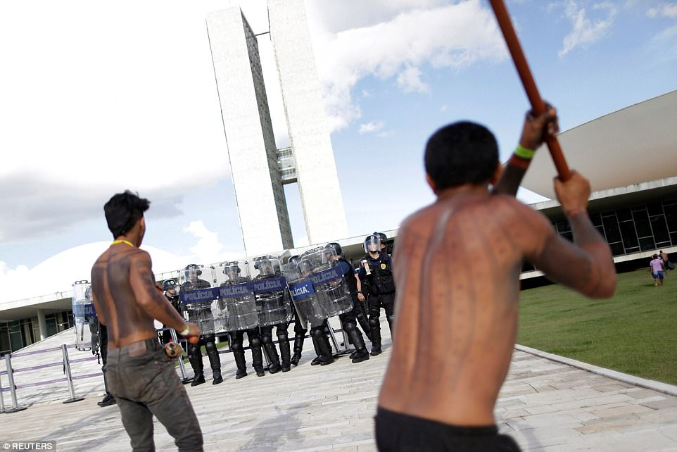 Police in Brasilia, the capital of Brazil, stand together and keep their shields close as members of the tribe stand poised with ancient weaponry