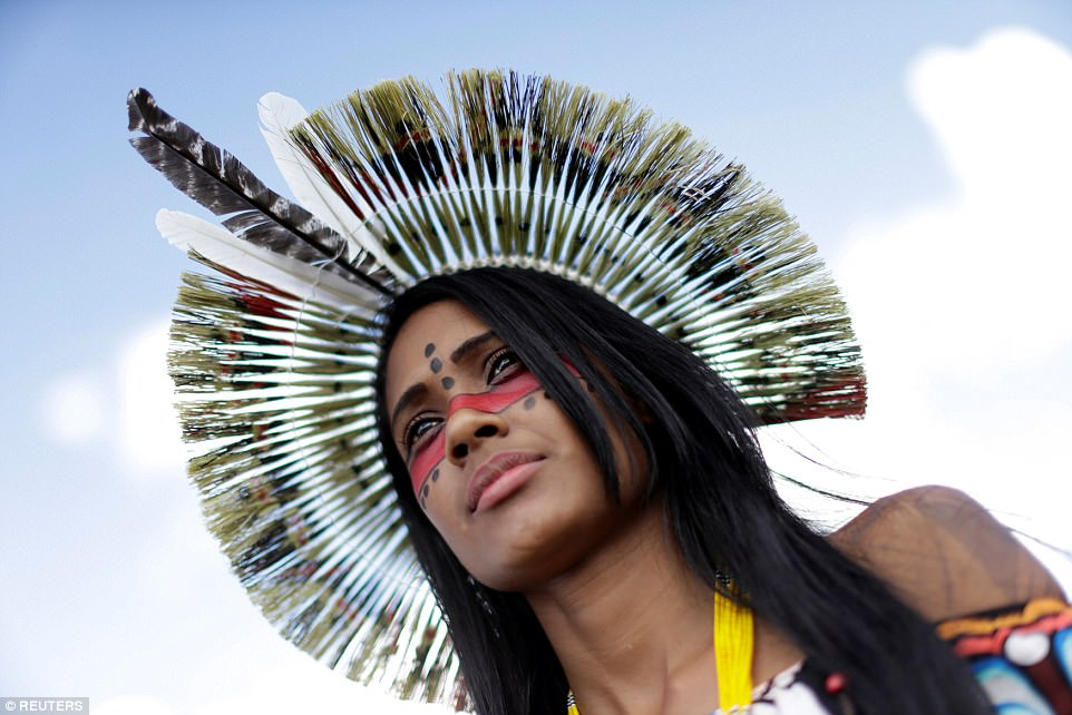 A female tribe member in traditional paint and headdress looks on during the protesting which will take place all week