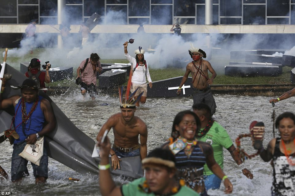 The tribespeople are forced to run through water as they escape tear gas which police have been using against them in ongoing clashes