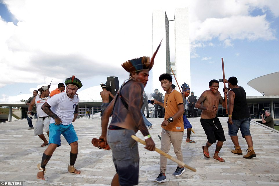 The tribesmen wear a mixture of traditional clothing and modern garb during the clashes which have been sparked over their desire to protect their long-held land