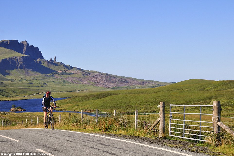 Natural wonder: A cyclist on the road at The Storr in Scotland's Isle of Skye  with the The Old Man of Storr pinnacle and Trotternish peninsula behind him