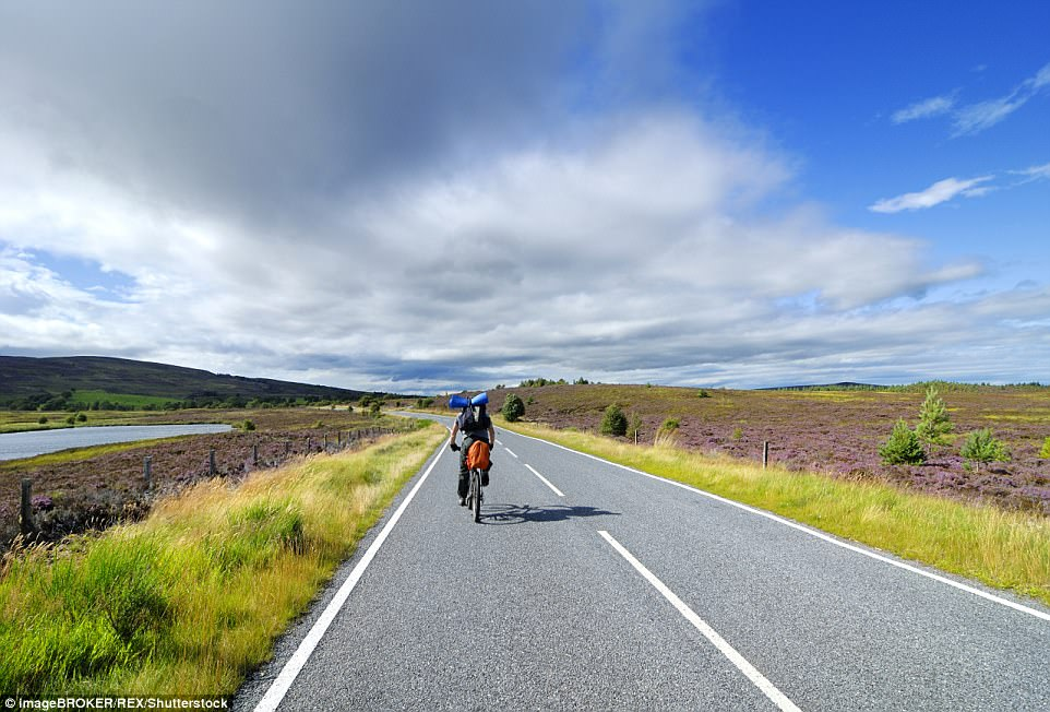 Picture perfect: A cyclist, prepared with camping gear, rides in the Grampian Mountains in Scotland with clouds above