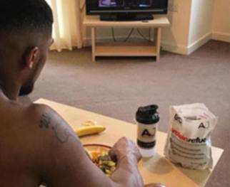 At 18, Anthony was a jobbing bricklayer devoting weekends to what he describes as ¿drink, clothes, clubbing, girls¿. Pictured: Eating in his living room