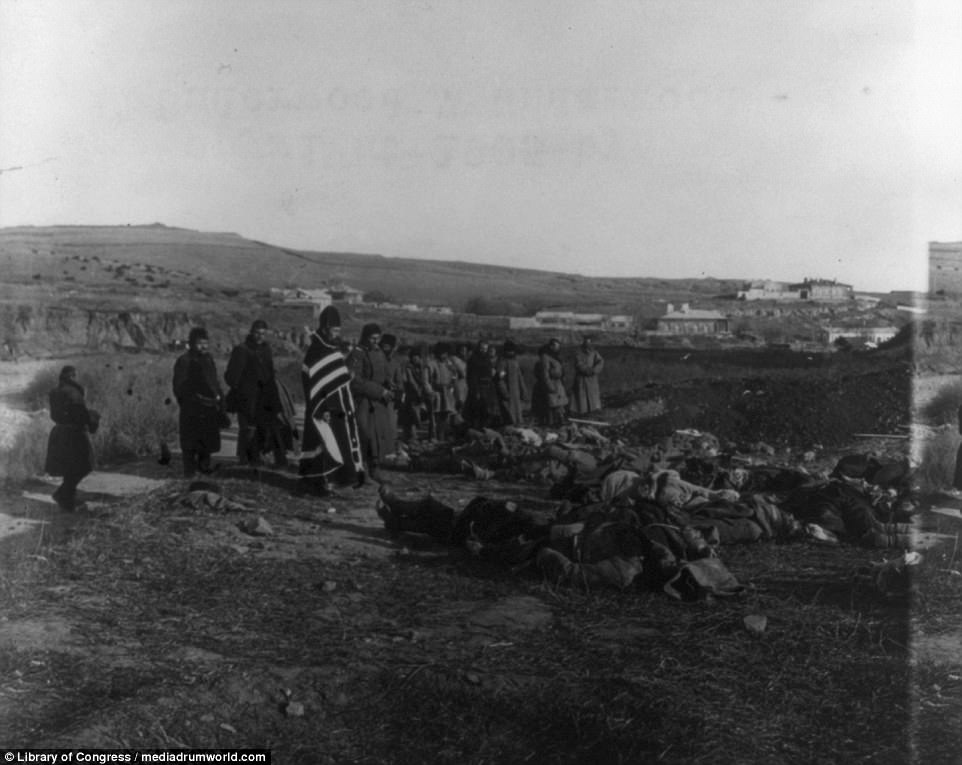 A priest and a group of Russian soldiers are pictured praying over the bodies of fallen Russian troops in Port Arthur, which was attacked by Japanese destroyers in an action which started the war between 1904 and 1905