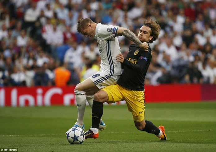 Real Madrid midfielder Toni Kroos holds off the Atletico Madrid danger-man Antoine Griezmann during the first-leg clash