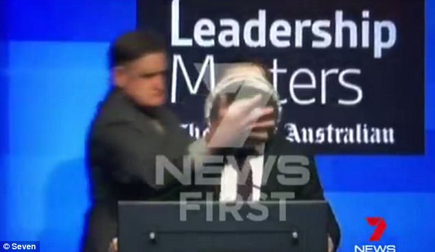 The man was seen walking up behind him, grabbing him by the shoulder and shoving the pie in his face