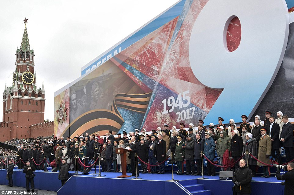 Vladimir Putin took to the stage to tell thousands of soldiers: 'We will never forget that it was our fathers, grandfathers and great-grandfathers who brought the freedom to Europe'