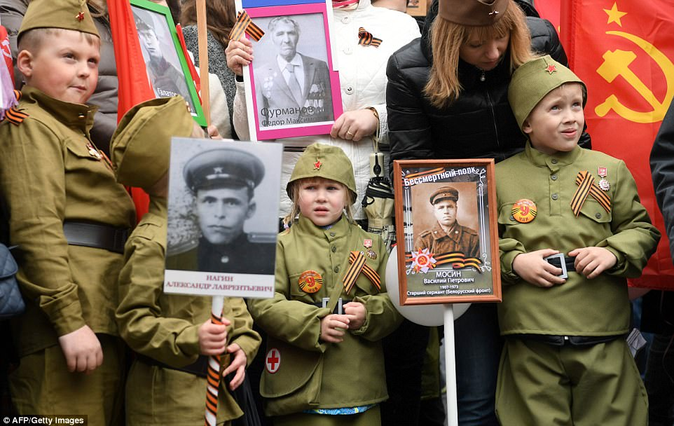 Children hold portraits of World War Two soldiers as they attend the Immortal Regiment march in central Moscow today