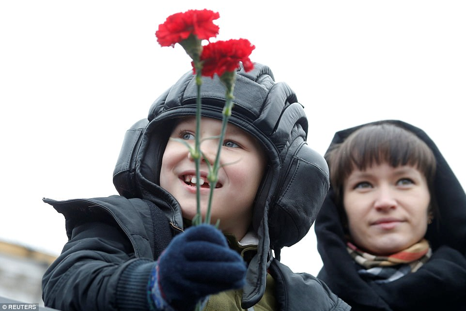 A young child holds red flowers before the parade marking the Second World War anniversary in Moscow this morning