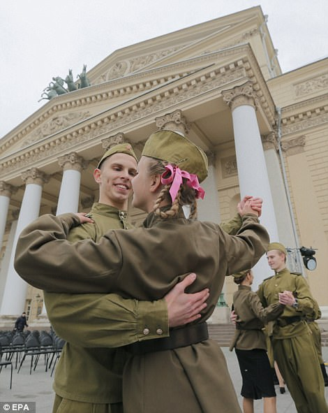 Russian young couples dressed in old style military uniform dance at a traditional veterans meeting point near Bolshoi Theatre in Moscow